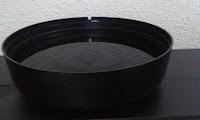 Plato negro lleno con agua filtrada para beber