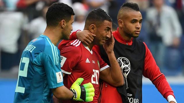 Morocco players console Aziz Bouhaddoz