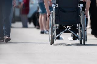 Person in wheelchair rolls down busy sidewalk - Person-first language