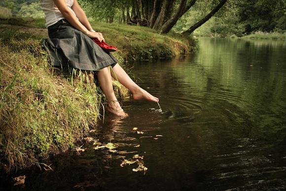 Mulher jovem com os pés nas águas de um rio