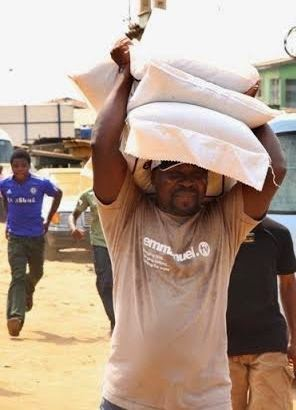 Photo  Of T.B. Joshua Carrying Three Bags Of Rice