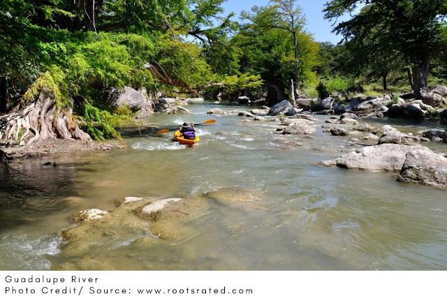 kayaker navigating through rocks in the river