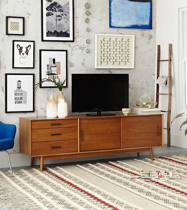 Salón con tv plana y pared con láminas y papel pintado