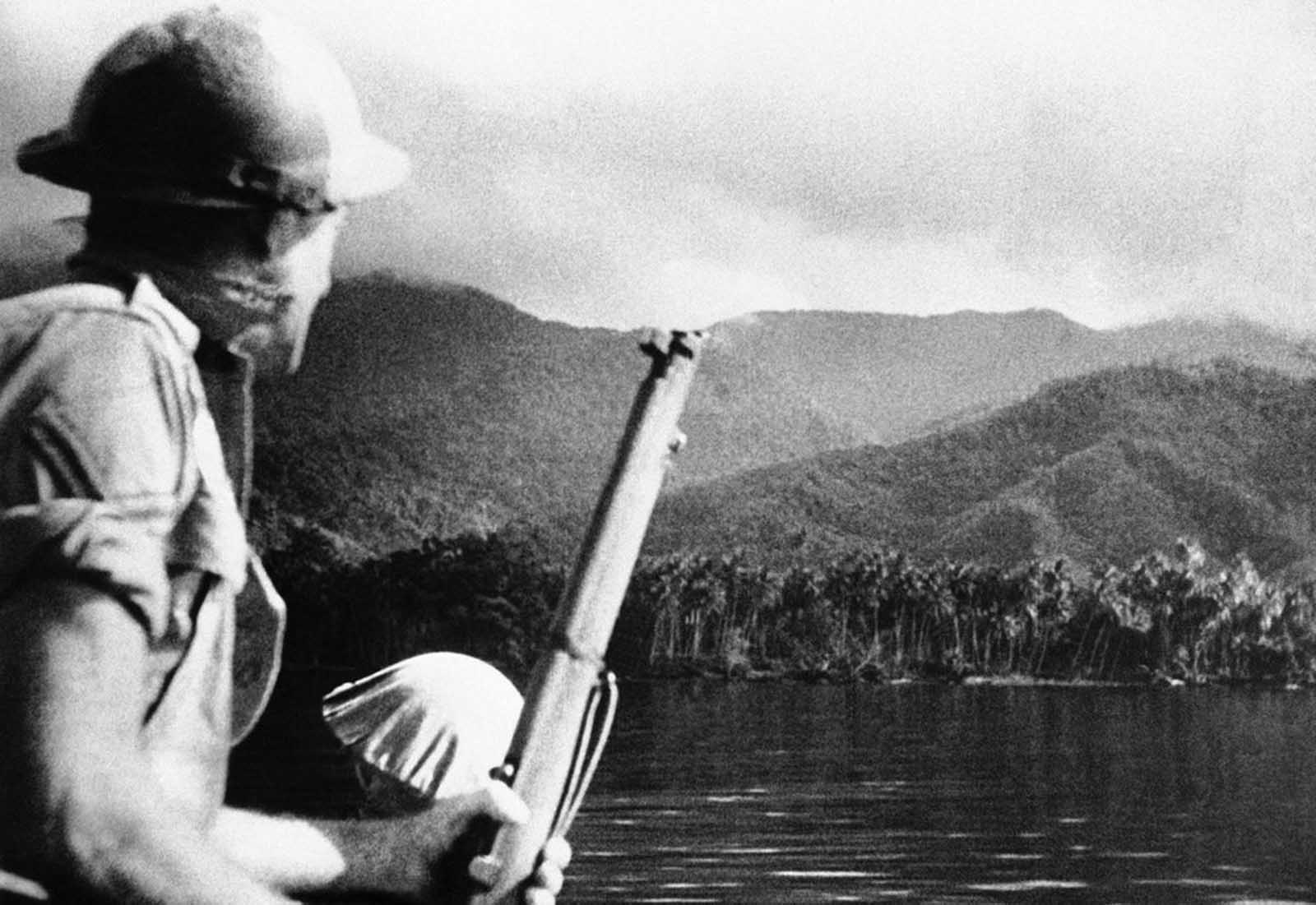 A helmeted Australian soldier, rifle in hand, looks out over a typical New Guinea landscape in the vicinity of Milne Bay on October 31, 1942, where an earlier Japanese attempt at invasion was defeated by the Australian defenders.