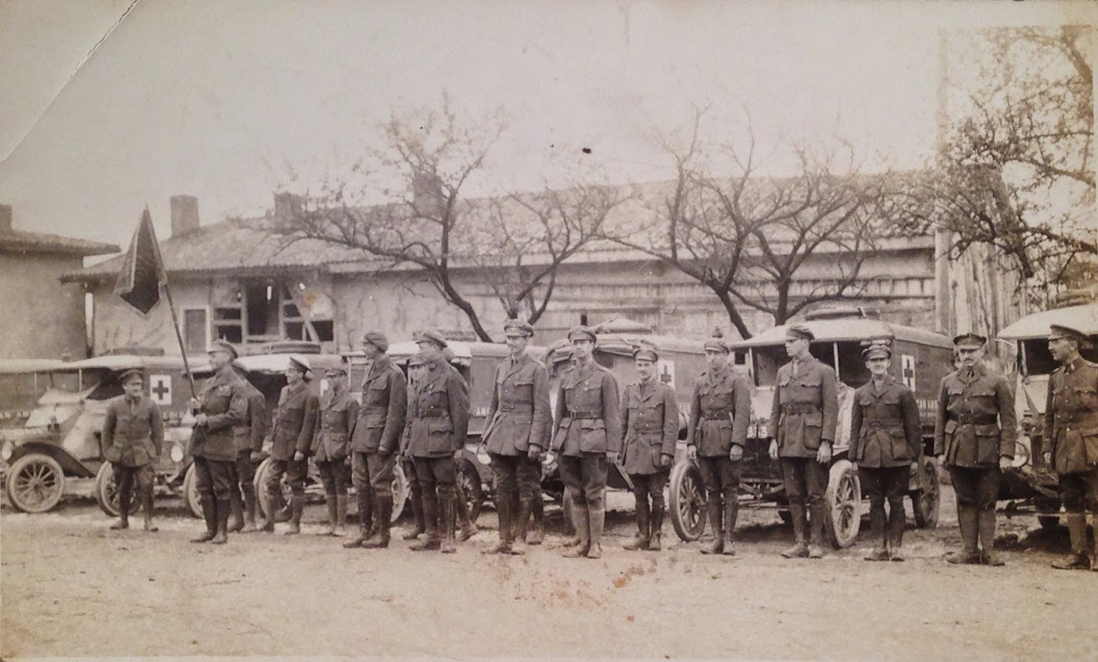 A photograph showing a line of men in uniform in front of ambulances.