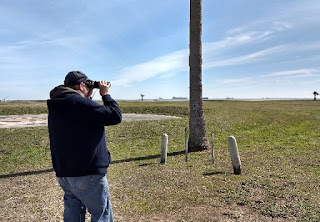 man with binoculars looking out to the Gulf of Mexico