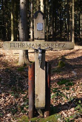"""Ein Holzkreut mit dem Schriftzug """"Fuhrmannskreuz"""" und einer Jesusfigur in der Mitte"""