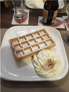 A photo of a Belgian waffle, served with powdered sugar, piped pastry cream, and beer. From the Leuven trip.