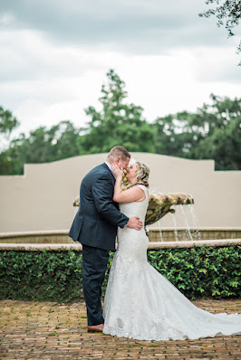 bride and groom kiss in front of fountain