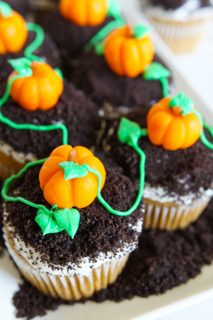 spiced pumpkin cupcakes, topped with buttercream, crushed cookies, and the cutest marzipan pumpkins | bakeat350.net