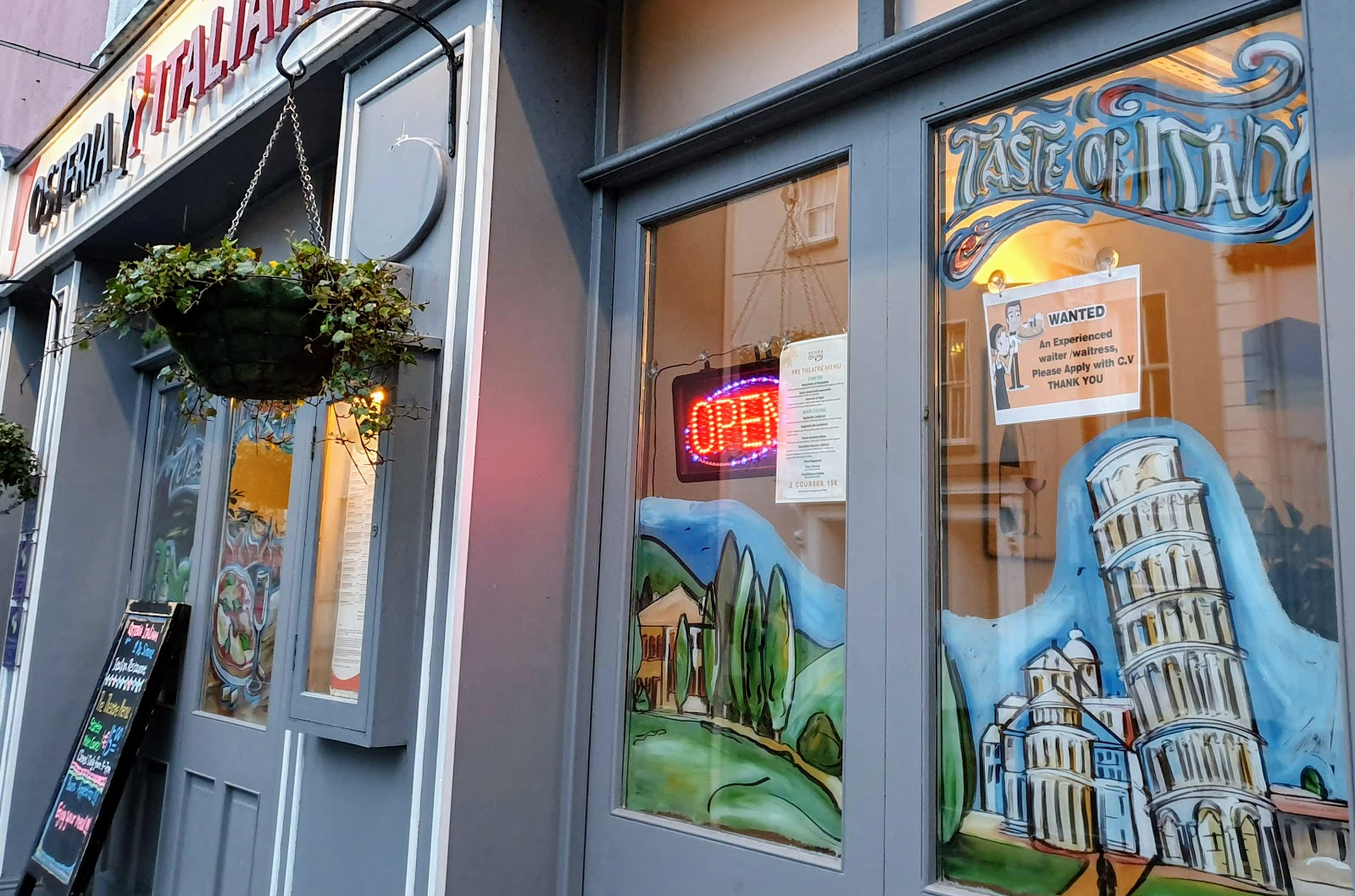 """Shop front of simon""""s Italian restaurant in Galway, with painted windows wigh the leaning tower of pizza and a red/blue neon Open sign illuminated."""