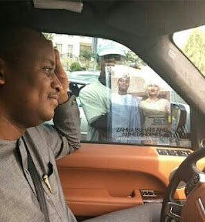 Zahra Buhari's husband, Ahmed Indimi pictured hiding his face in traffic as vendor holds out magazine featuring wedding .