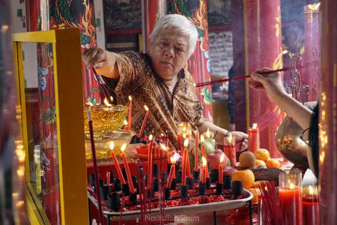 Membakar hio di kelenteng Fuk Ling Miau Jogja