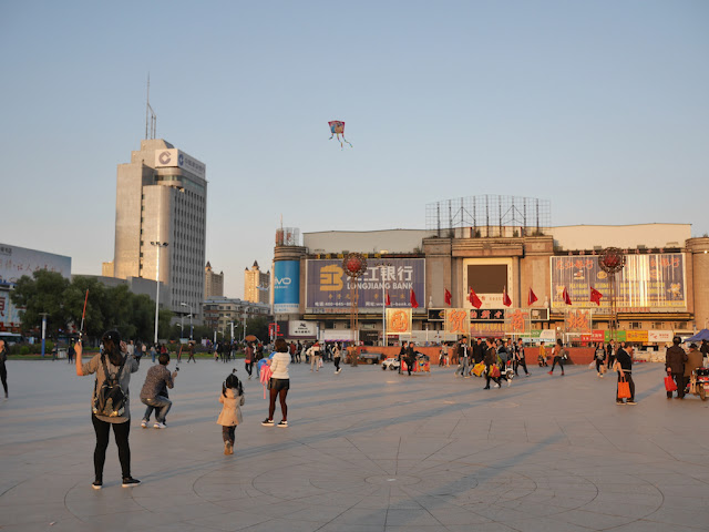 Girl flying kite at Culture Square (文化广场)  in Mudanjiang, China, with sign for the Guomao Shopping Center (国贸商城) in the background