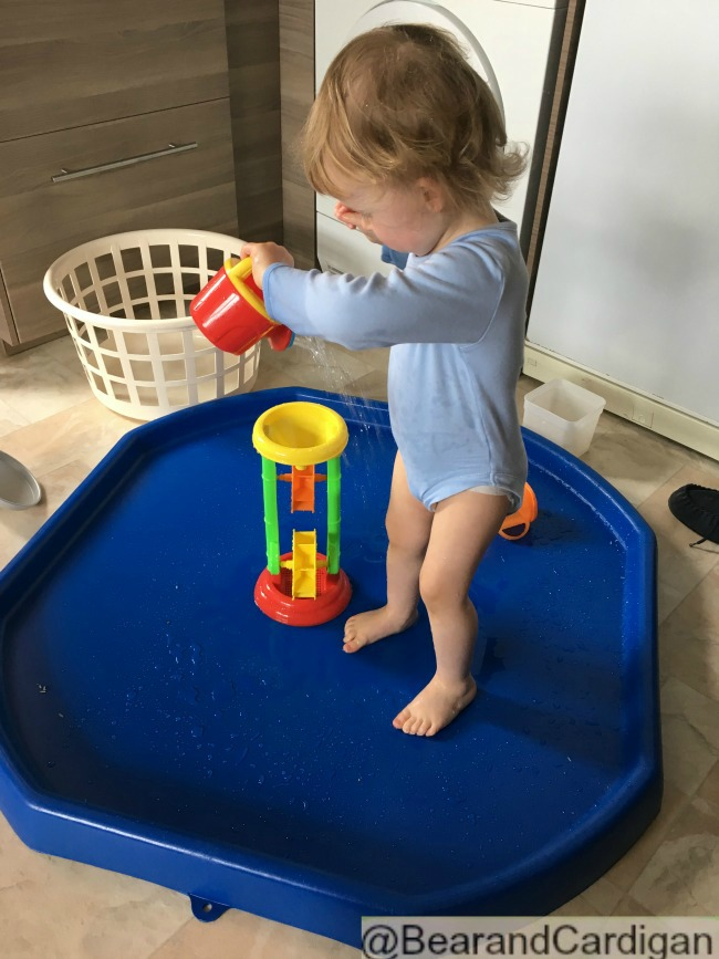 A Very Quiet Week. Just Sand and Water A toddler pouring water from a watering can onto a watermill standing in a  blue tray