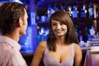 Esto es una chica en un bar que esta ruborizada, se dirige a un chico y le dice toda indignada:  - Manolo, cariño, tienes que decirle un par de cosas a ese tipo de ahí, me ha estado insultando.