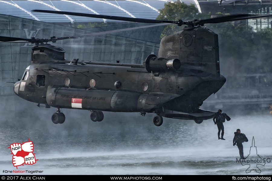 Navy Divers deploying from the rear ramp of the CH-47D Chinook while the helicopter hover steadily a few meters above the water surface.
