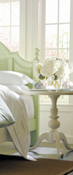 mint green wooden bed, white walls