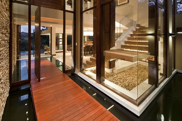 Entrance into the house with small walkway surrounded with watter at Contemporary South African SGNW House by Metropole Architects