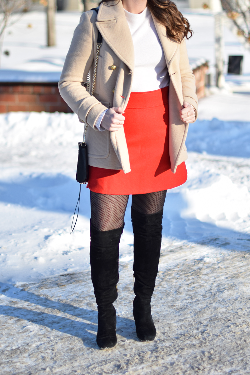 Cream sweater, red skirt, and tan peacoat on young woman.