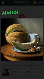На столике  лежит разрезанная дыня, кусок который на тарелке и чашка с напитком рядом