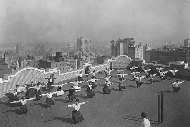 Original caption: Physical training twenty-two stories in the air. Men and girls employed by the New York State Industrial Commission going through physical exercises designed for the National Security League, on the roof of the Victoria Building in New York.