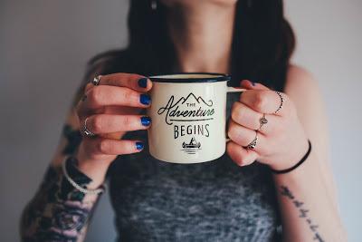 Mujer tatuada tomando café