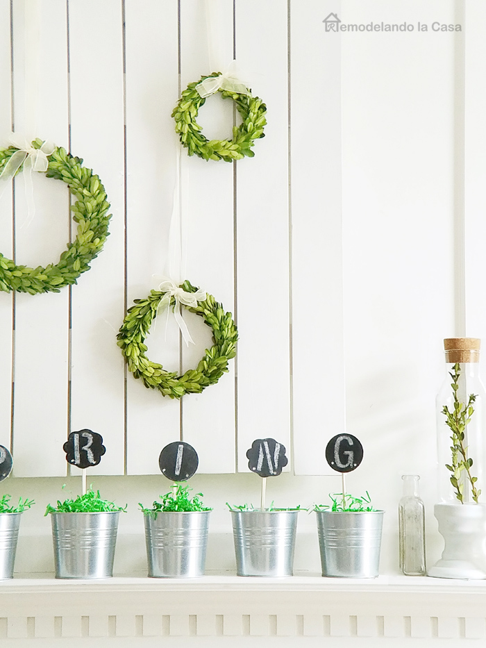 boxwood wreaths on mantel with galvanized plant post and Spring sign