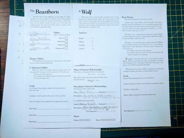 "Two sheets of paper, one titled ""The Beastborn"" and the other ""A Wolf,"" with various details of the characters on it"