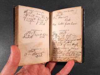 An open book of handwritten entries attached to printed dates.