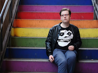 A close up of a guy staring outwards with round brown and green glasses with quiffed light brown hair, black leather jacket, blue shirt, black tshirt with a white skull on the front of it and bright blue chinos sat on rainbow coloured steps on a brigth background.