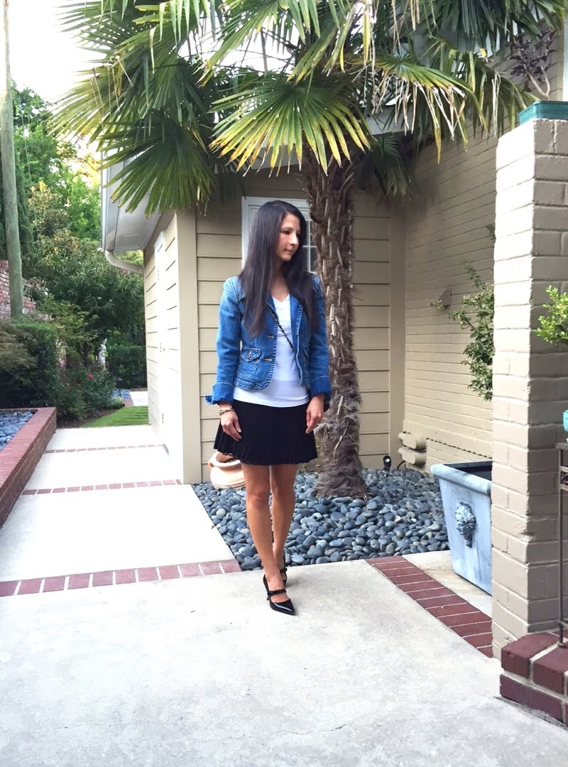 Wearing denim jacket, white tee, black pleated mini skirt and black mary janes with a black crossbody bag.