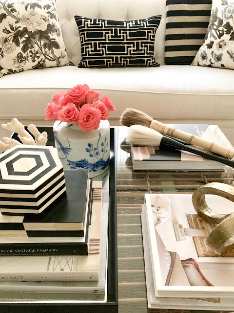 Layered books and decor in a black tray upon an ottoman in a living room designed by Sherry Hart. Come discover more inspiring trays for layering and vignettes in Adding Tray Très Chic to Your Home.