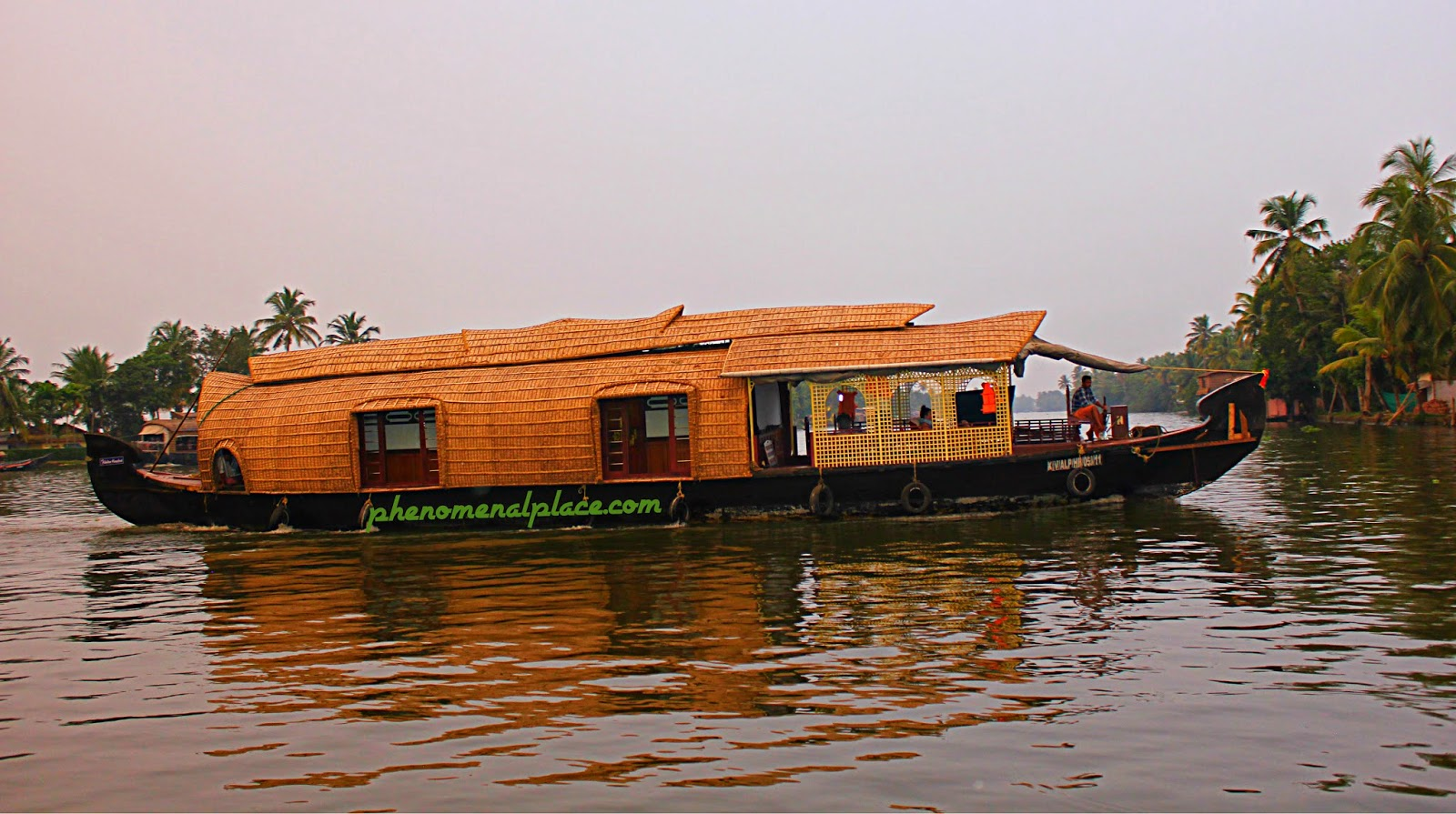 A Houseboat Sails Majestically Through The Backwaters Of Alleppey
