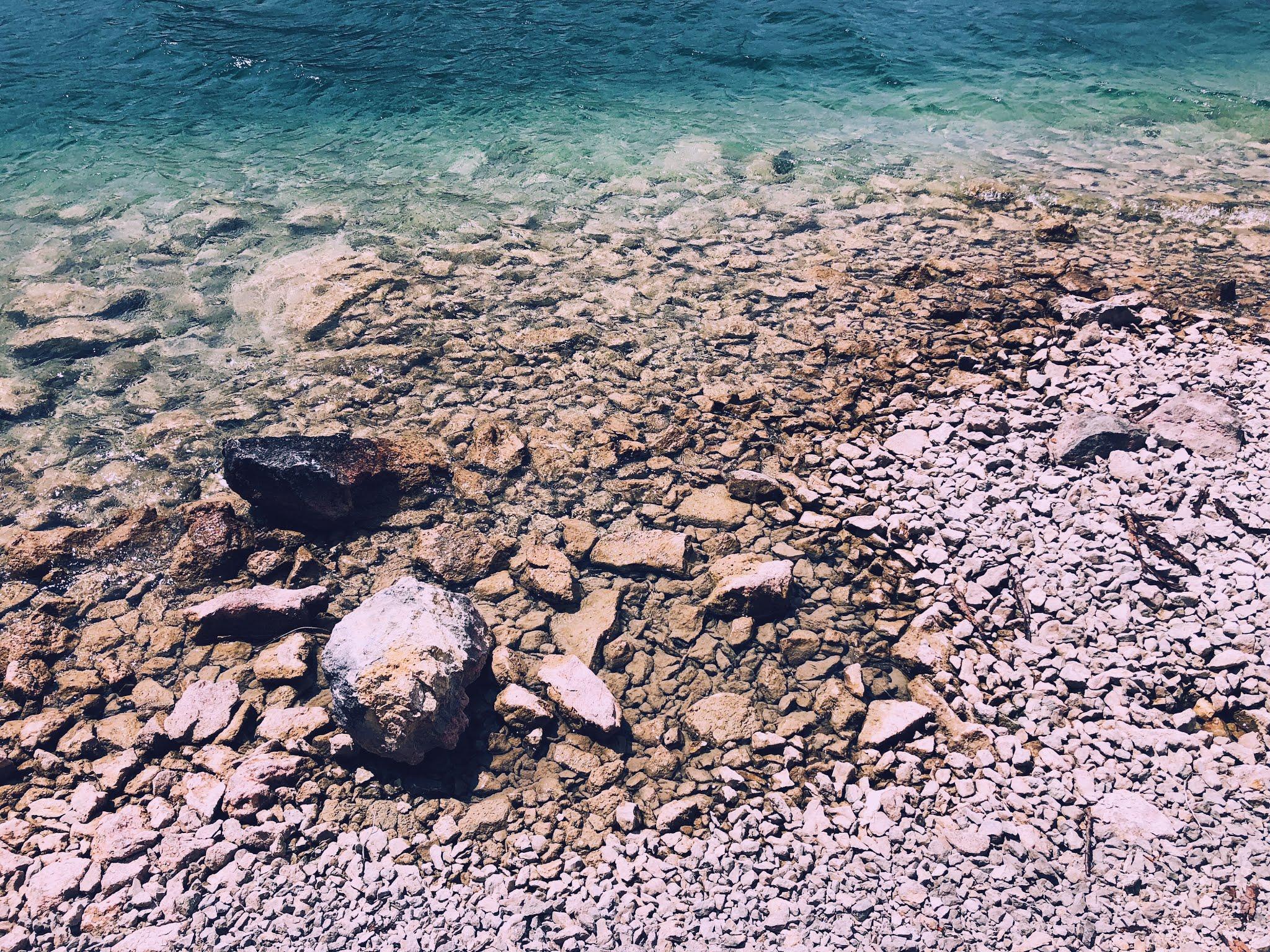 Helderblauw water met stenen of de voorgrond