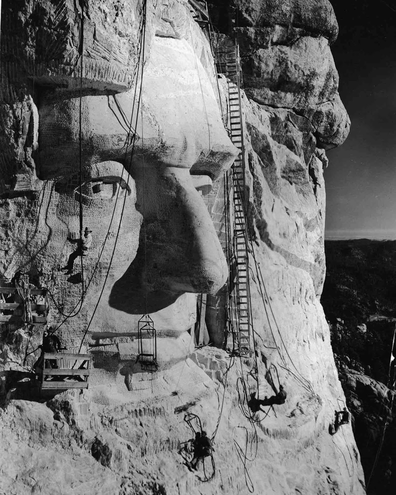 Gutzon Borglum hangs below an eye as his crew works on Abraham Lincoln's head. 1935.