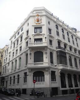 Chaflán del edifico entre las calles Clavel y Caballero de Gracia. En la parte superior, el escudo policromado del Reino de España.