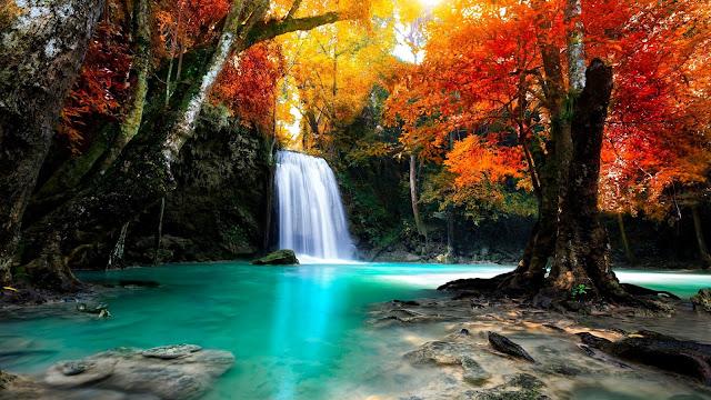 Foto met een waterval en gekleurde herfstbladeren
