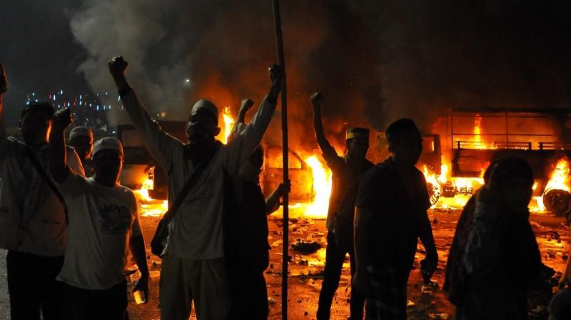 Sejumlah pendemo berteriak di dekat mobil yang terbakar di kawasan Monas