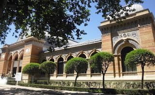 Rodeado de jardín, edificio de una planta con exterior de ladrillos de dos colores y azulejos de cerámica pintados.- Grandes arcos en puertas y ventanas y cubierta metálica.