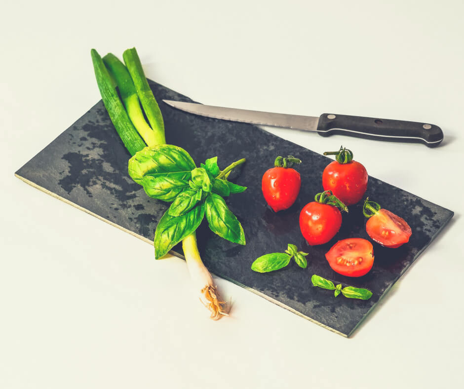 A black chopping board with spring onions, herbs, and tomatoes on it, with a knife sitting nearby. Foods I want to teach my children about how to cook.