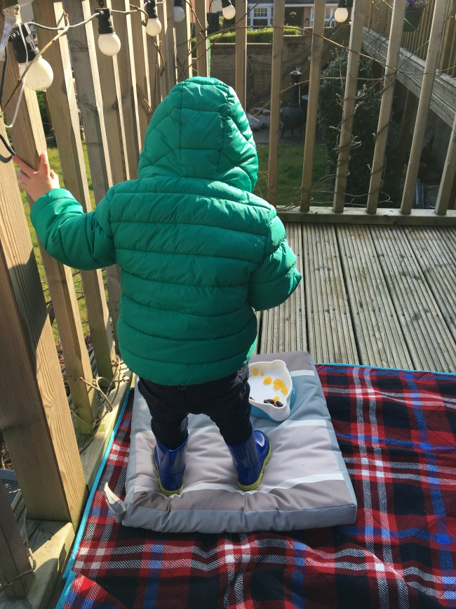 blanket on floor with cushion and toddler stood on cushion. Little bowl of nibbles at his feet
