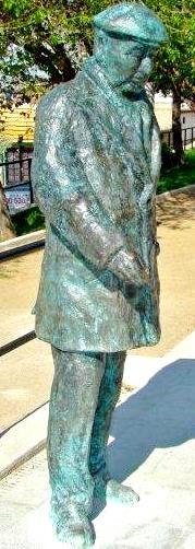 Monumento de Pablo Neruda parado y con saco y boina