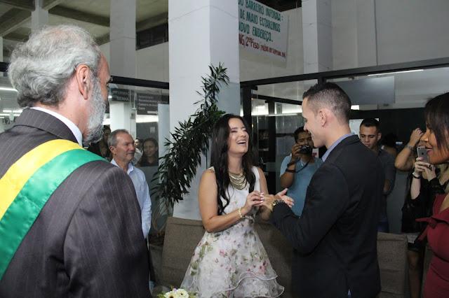 sorrindo ao colocar aliança no dedo do noivo