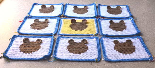 A wider view of the nine squares arranged 3 x 3, all being white with tan circles and blue borders except for the centre square which is yellow with a white and blue border. All squares have half-circle tan ears stitched to them. The viewpoint is low with the bottom of the arrangement in the foreground so that one is looking across the top of the squares to see the ears raised above them.