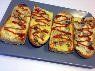 Zapiekanka, czyli klasyczny polski fastfood w postaci bagietki z pieczarkami i żółtym serem. Całość doprawiona katchupem