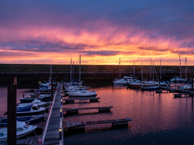 Photo of a colourful sunset over Maryport Marina