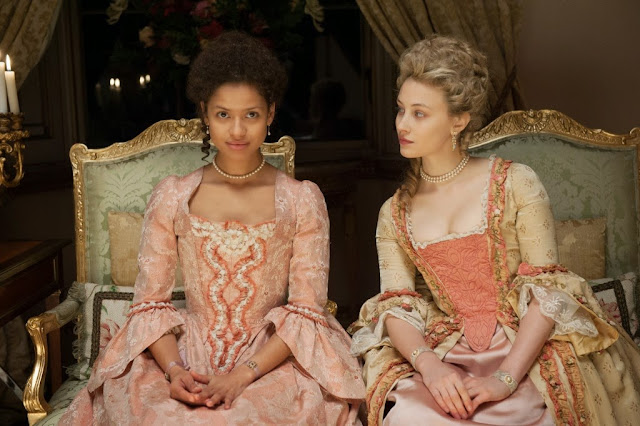 Gugu Mbatha-Raw and Sarah Gadon sit patiently between takes at the shoot of Falco's 'Rock Me Amadeus' video.