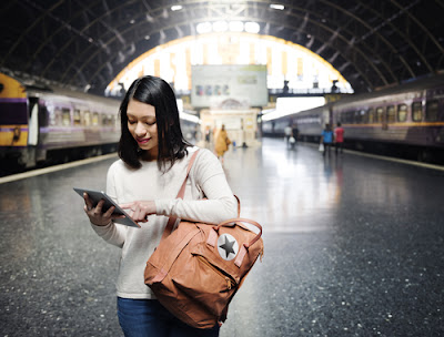 Woman in train station with device
