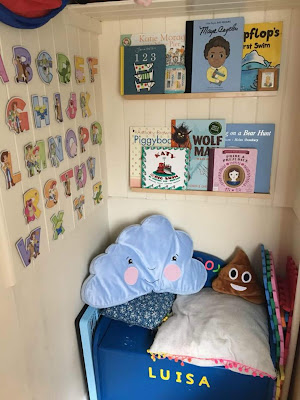 A child's reading corner with a seat, cushions and book shelves.